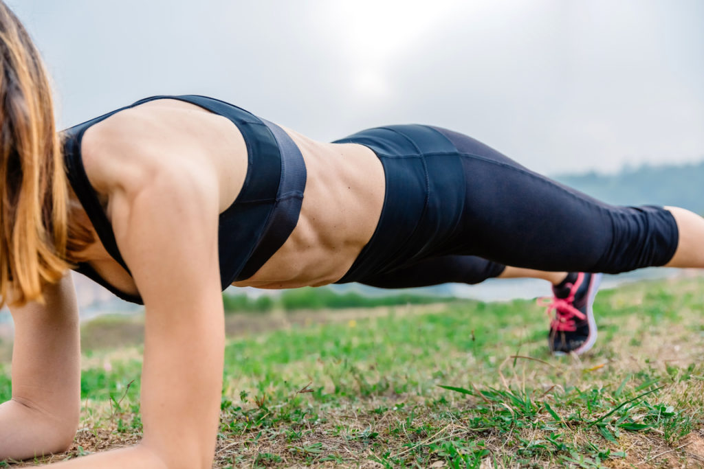 Female athlete doing plank, training for the whole body