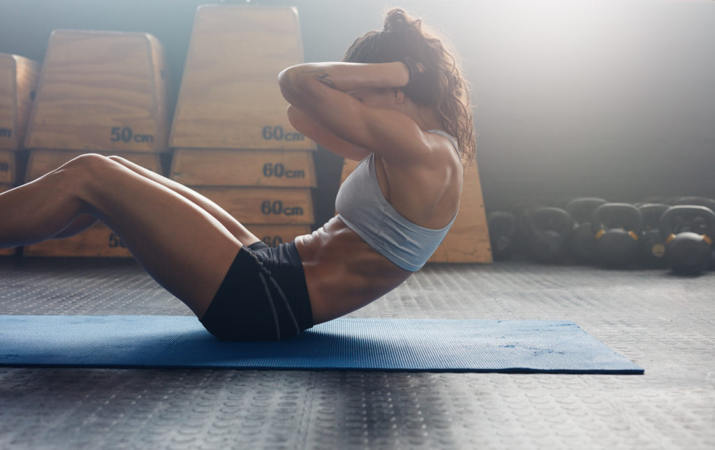 Fitness woman doing sit ups in bending-forward motion