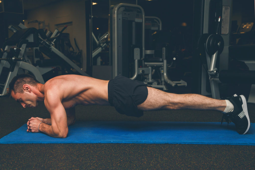 Man doing plank on his elbows with his body in a straight line