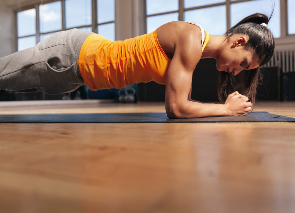 Woman doing plank very focused and concentrated, challenging her mind.
