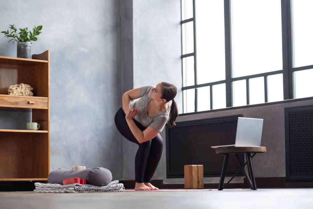 Woman doing morning yoga and performing Parivritta Utkatasana or Chair Twist yoga pose