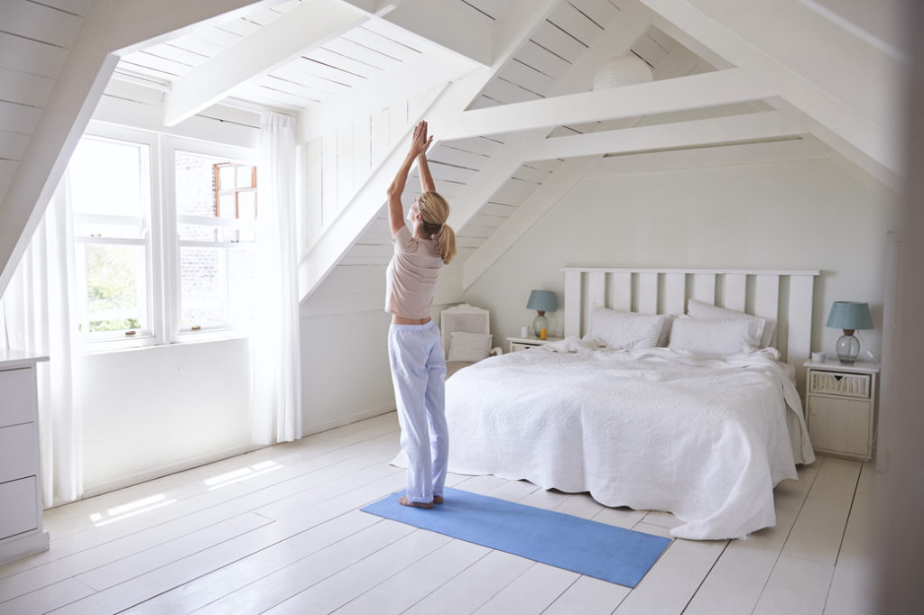 Woman At Home Starting Morning With Yoga with Sun Salutation