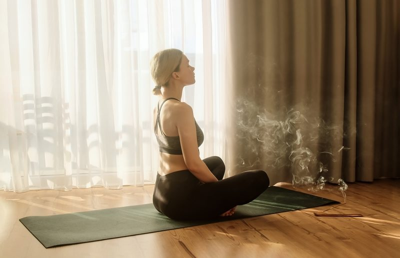 woman doing yoga and meditating home in a quiet space