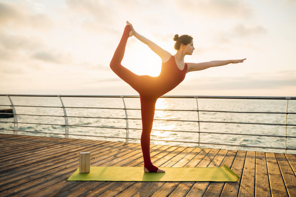 woman doing yoga in the morning at the sea on sunrise in dancer pose (natarajasana)