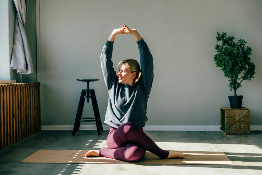 Woman doing yoga in the morning indoors in cow face pose (gomukhasana) for physical and mental health benefits