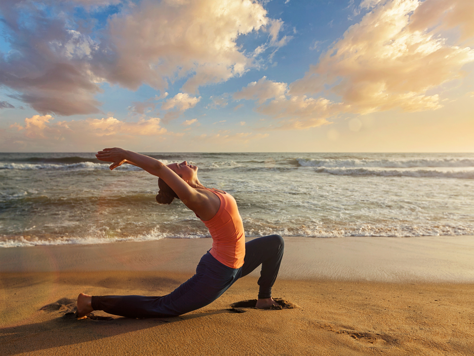 Woman practices yoga at beach on sunrise at the sea and performing the crescent lunge pose (anjaneyasana )