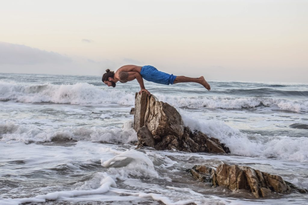 what-is-yoga-origin-hisotry-man-doing-peacock-pose-surrounder-by-water-life.jpg