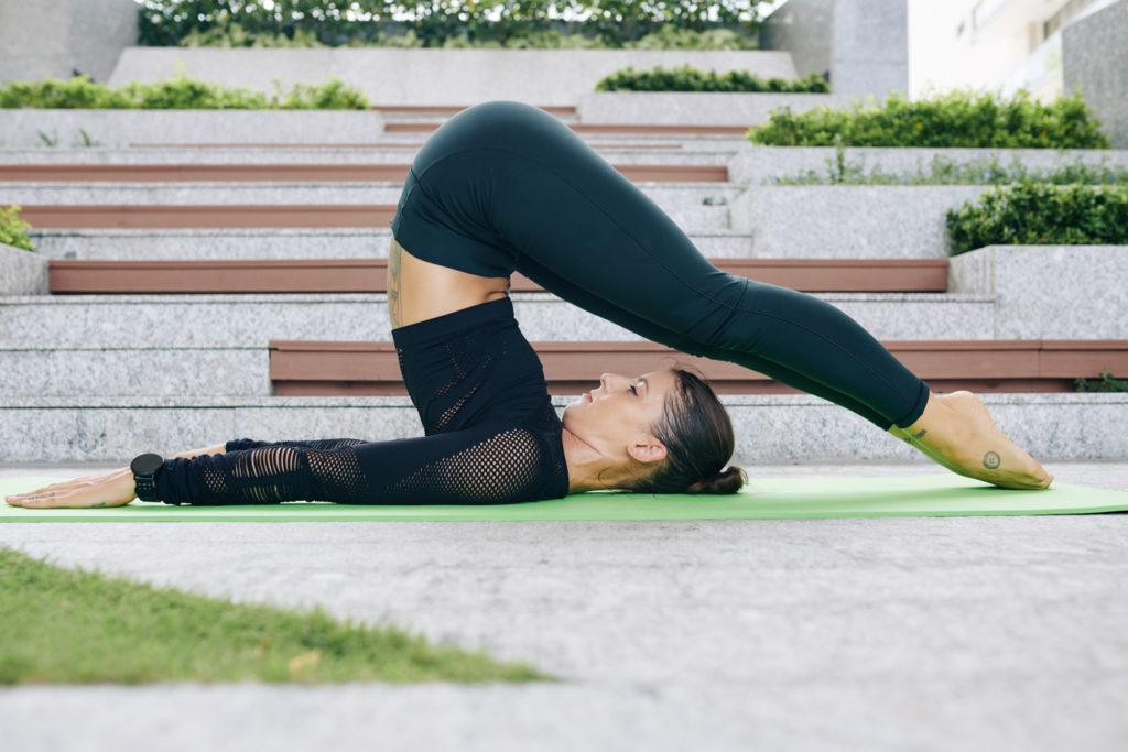 woman-practicing-yoga-doing-plow-pose-Halasana-relieve-stress