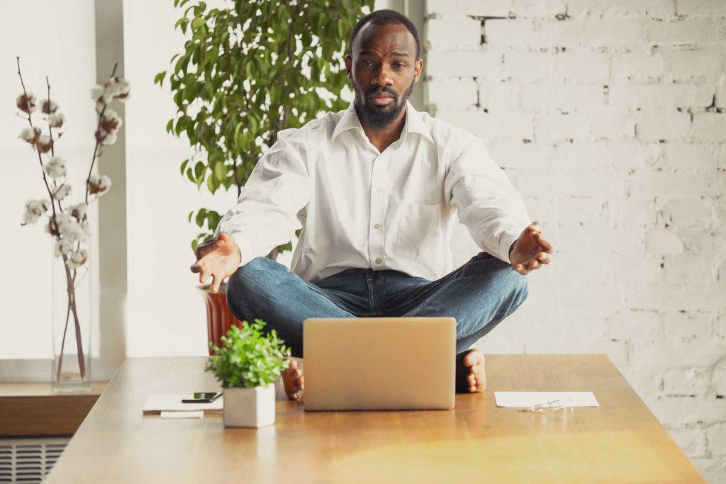 young-man-doing-yoga-at-work-balance-decrease-stress-improve-satisfaction-harmony